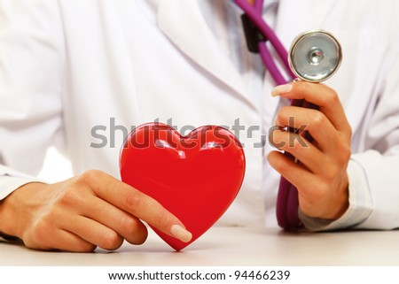 A  female doctor examining a red heart