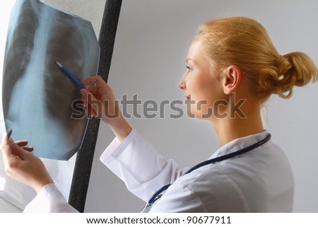 A female doctor examining an x-ray picture