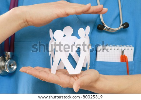 A female doctor holding paper people, focus on the hand, closeup