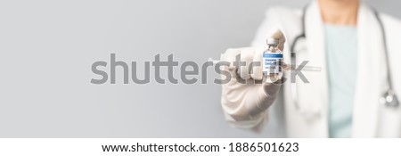 A female doctor in white gown showing updates safe and effective mRNA Covid-19 Vaccine vial - The successful vaccination from COVAX collaborating. Hope, Pandemic, Global Vaccine Action Plan, Banner.