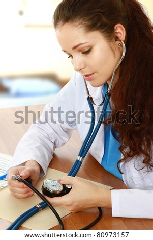 A female doctor is measuring pressure at the desk, indoors