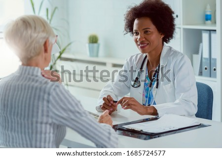 A female doctor sits at her office and examining elderly female patient