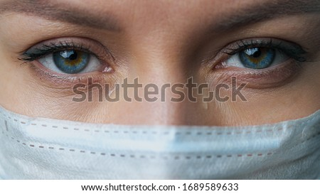 A female doctor therapist in a white robe, mask and gloves. Face close-up. The doctor cries and prays. Tears in eyes. Regret, anxiety and despair. Pandemic and virus epidemic. Coronavirus covid-19.