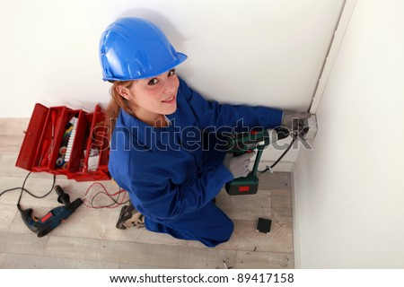 A female electrician at work. - stock photo