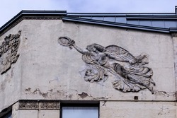 A female figure with wings, a muse with a wreath and a laurel branch on the facade of a historic building. Destruction of architectural decorations