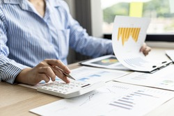 A female financier is reviewing company financial documents, monthly financial statement summary from the finance department. The concept of managing the company's finances for accuracy and growth.