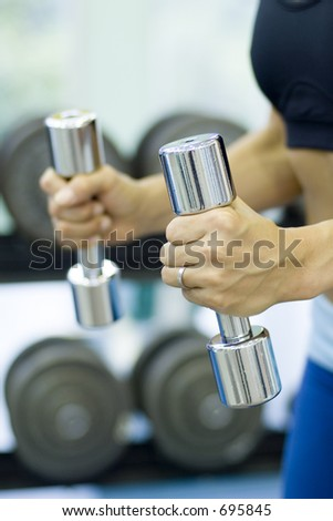 A female fitness instructor holds a pair of chrome dumbbells in the gym