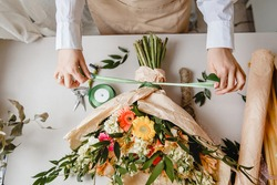a female florist ties a ribbon bow on a bouquet of flowers wrapped in craft paper on the desktop. Top view. High quality photo
