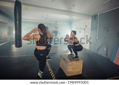 A female group having functional fitness training doing standing crunches and step up in sport gym Foto stock ©