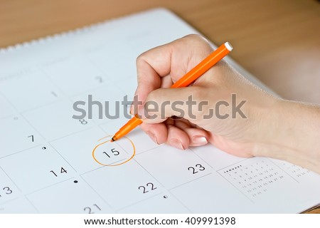 A female hand circling the date of the 15th day in the calendar #409991398