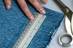 A female hand holding a ruler in place on denim jeans material with scissors in at one side