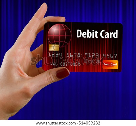 A female hand holds a debit card that is red and black. in front of a blue curtain. This is a photo illustration combining photographs with artwork and is free of copyright.