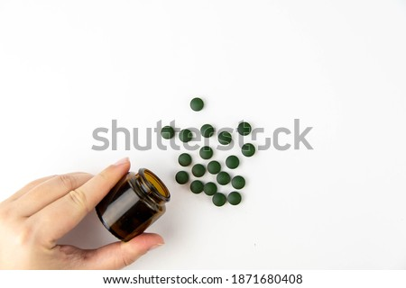 A female hand holds a jar of pills, near scattered green spirulina pills on a white background. Foto stock ©