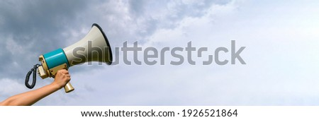 A female hand holds a megaphone. Horn loudspeaker is big and old. Clouds background. The concept of a message in business, loudspeaker, attracting attention.
