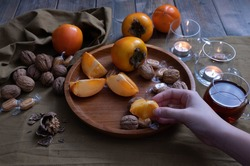 a female hand holds a piece of persimmon, nuts on the table, a candle and decorations are burning next to it on a green background
