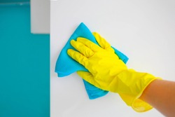A female hand in yellow rubber gloves wipes a modern white kitchen with a microfiber cloth.