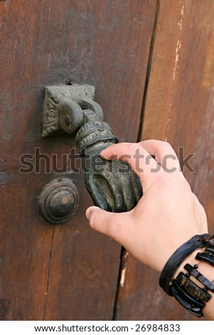 A Female Hand Knocks An Old Fashioned Hand Door Knocker