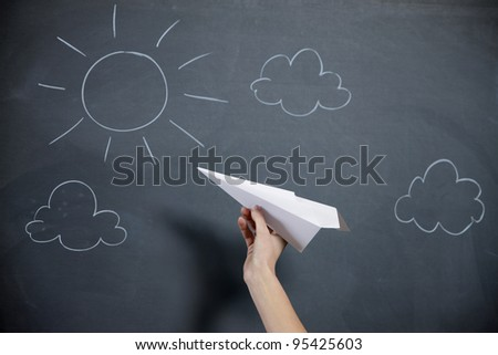 A female hand prepares to launch a paper airplane. Blackboard with sky and sun on backgroud