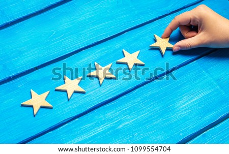 A female hand puts the fifth wooden star on a blue background. The critic sets the quality rating. Five stars, the highest quality mark. Raising the rating level of the hotel, restaurant, cafe