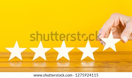 A female hand puts the fifth wooden star on a table #1275924115