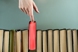 A female hand selects a brightly red book to read from a series of books. Top view, close up