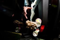 a female hand throws a handful of garbage accumulated in the car at the open door of the car - coffee glasses, bags, crumpled paper. Flying objects are slightly blurred to enhance the effect of