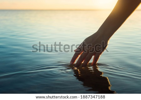 A female hand touching the ocean water in front of a beautful sunset during summer time.