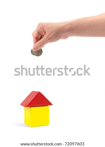 A female hand with coin and a toy house isolated against a white background
