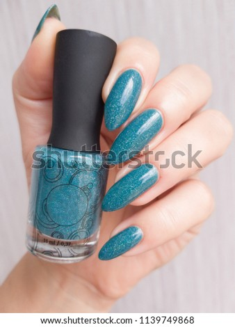 63b156162dd3 A female hand with long nails holds a bottle with a light blue nail polish