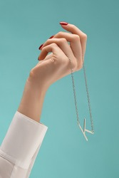 A female hand with red manicure is holding a silver chain with a pendant in the shape of a letter K. The necklace is hanging from the wrist on the blue backdrop.