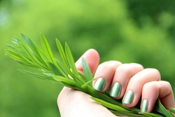 A female hand with spring green (mint coloured) nail polish on holding a twig against a green background - eco-friendly nail polish
