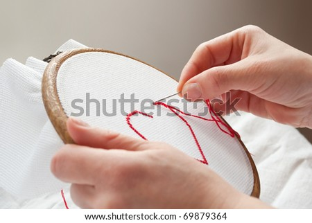 a female hands embroidering red heart