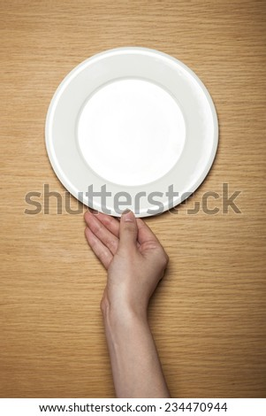 Top view of hand hold a empty bowl on wood Images and Stock