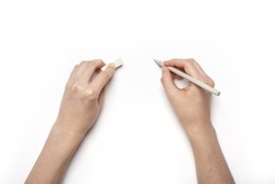 A female hands hold(pick up) grey pencil and eraser isolated white, top view at the studio.