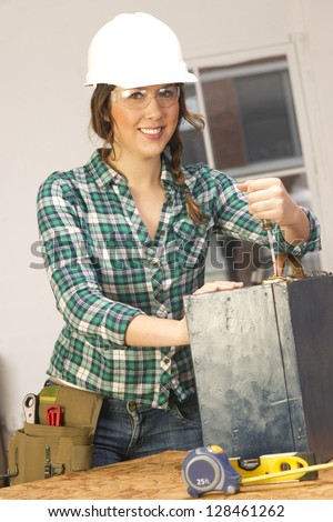 A Female handy with tools works on a repair project in the shop