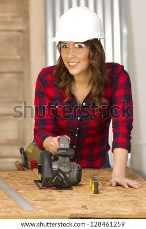 A female handy woman works on a building project in the shop sawing cutting boards