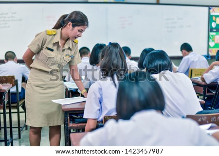 A female high school teacher in Thai government teacher uniform is teaching in the classroom. The sign of Thai government is on her belt. The colour bar on the shirt is Thai government officer sign.