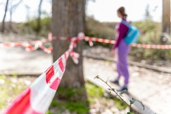 A female hiker behind a barricade tape at a restricted hiking area