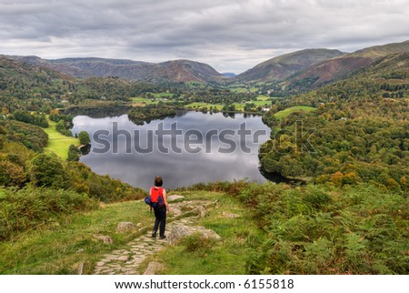 A female hiker descending the path from Loughrigg with Grasmere in the background