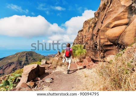A female hiker on mountain path bordered by red cliffs, Tenerife in the Spanish Canary Islands