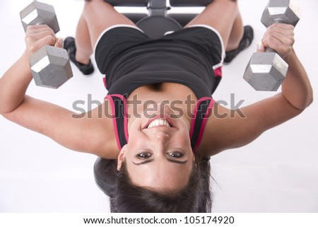 A female in gym action lifting barbells for fitness sake laying weight bench