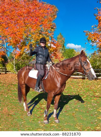 A female jockey on horse in a beautiful autumn day.