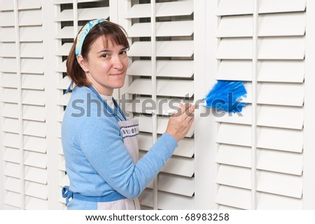 A female maid dusts window shutters with a feather duster