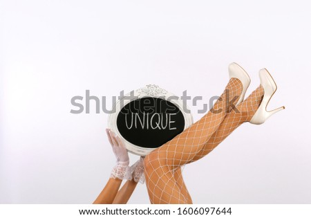 A female model's long legs are stretched out high in  a vertical form in front of a white background. Her  legs are decorated with a chalkboard sign with the words unique written on it.