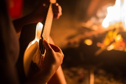 A female musician playing guitar outside, sitting next to a fire. Relaxation.