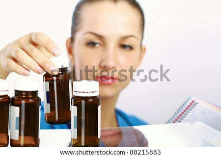 A female nurse giving bottle pill isolated on white background