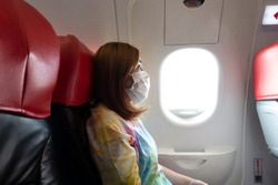 A female passenger traveler wearing mask to protect Corona Virus or Covid-19 and sitting in airplane.