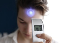A female person being measured body temperature with a contactless thermometer