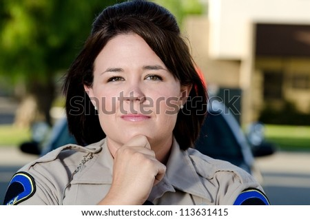 a female police office with a serious look on her face as she thinks of something.
