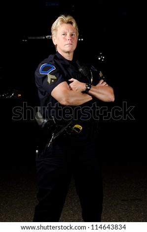 A female police officer in the night during her shift.